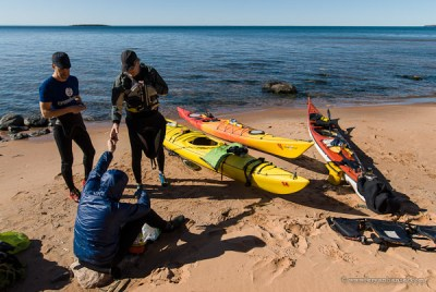 kayakers on a sand beach in the Apostle Islands.