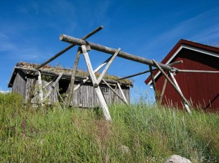 An old cod drying rack in front of a traditional sod roof house.