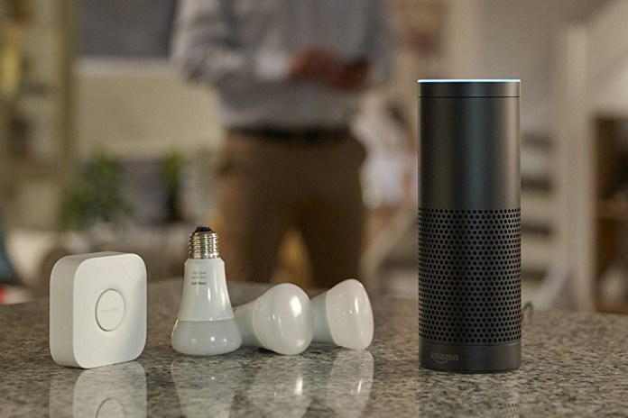 An image of an Echo on a counter top next to a few Hue bulbs