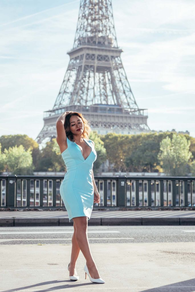 portrait of woman in front of the eiffel tower in paris with a telephoto angle 70mm focal length and with partial tower visible and looking bigger in the background