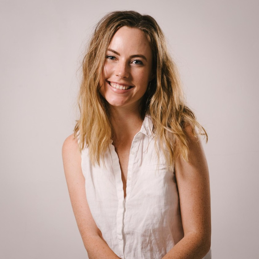 Headshot of lifestyle photographer Paige Gribb in a white sleeveless collared shirt