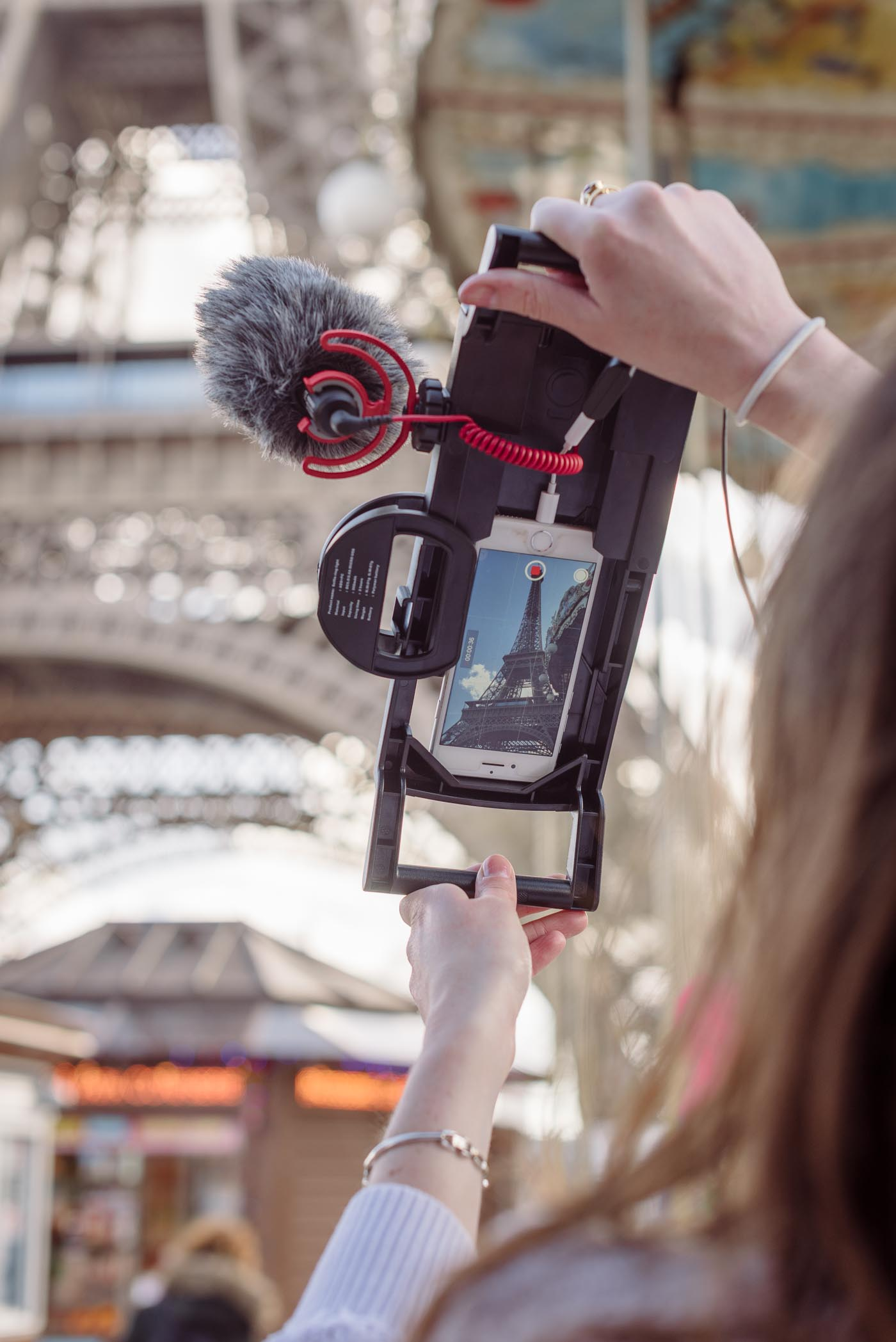 Model holding iphone filming case with phone and microphone and mini ring light to film Eiffel tower vertically in Paris, France