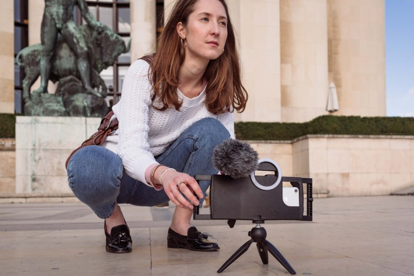 real-life product photography of woman using iphoneography equipment to film in Paris, France
