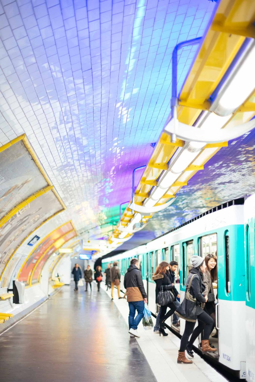 Young people in fall weather attire getting onto the metro under purple and teal neon lighting at the Odéon metro station in Paris, France