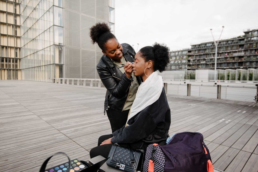 behind the scenes shot of makeup artist Emeline Ciani prepping model Safia Abdou for the photoshoot