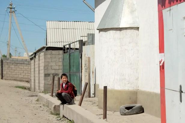 Un bambino appena uscito da scuola fuori dal Dordoy Bazaar