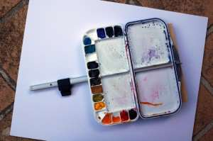 Plastic watercolor palette attached to its support arm before insertion into plein air easel tripod