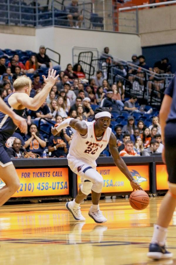 Keaton Wallace dribbles towards the basket.
