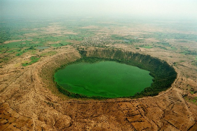 Lonar Lake is a saline soda lake located at Lonar in Buldana district, Maharashtra, India, which was created by a meteor impact during the Pleistocene Epoch.[1] This lake, which lies in a basalt impact structure, is both saline and alkaline in nature. Geologists, ecologists, archaeologists, naturalists and astronomers have reported several studies on the various aspects of this crater lake ecosystem.[2] Lonar Lake has a mean diameter of 1.2 kilometres (3,900 ft) and is about 137 metres (449 ft) below the crater rim.