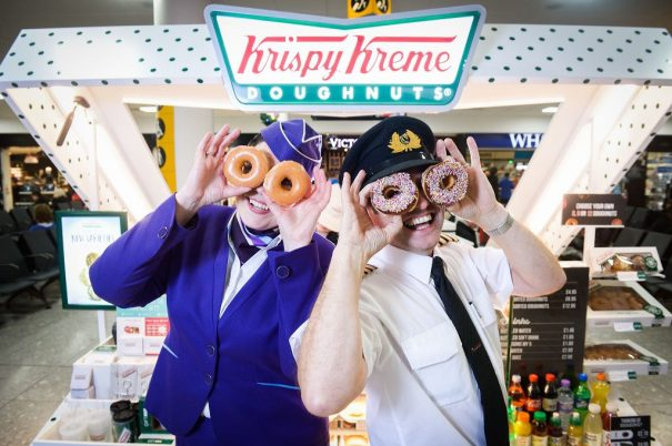 Picture by Nick Ponty 19/11/16 Krispy Kreme opens at Glasgow Airport Logan Air Cabin Crew manager Avril McEwan and Pilot Eddie Watt try out some doughnuts.