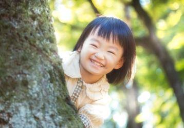 「木陰からニコニコ笑顔の小さい女の子」のフリー写真素材