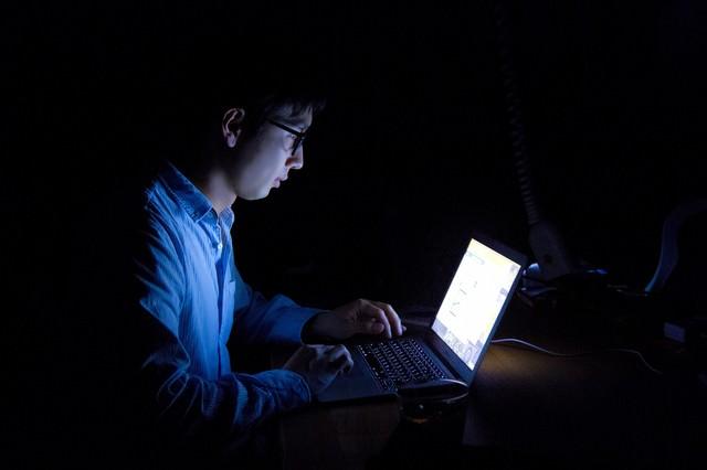 暗闇�PCを使�残業中�男性