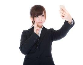 「自撮りをする女性の新入社員自撮りをする女性の新入社員」[モデル:河村友歌]のフリー写真素材