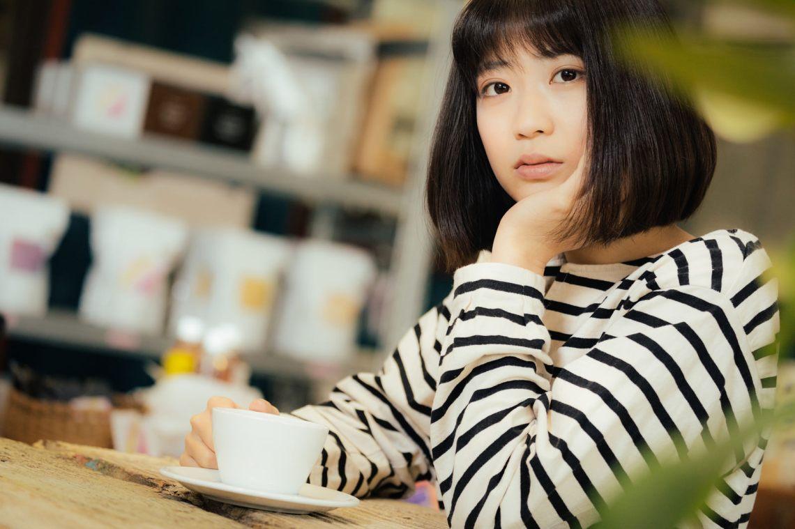 「カフェで退屈そうにこちらを見つめる女性」の写真[モデル:塩田みう]