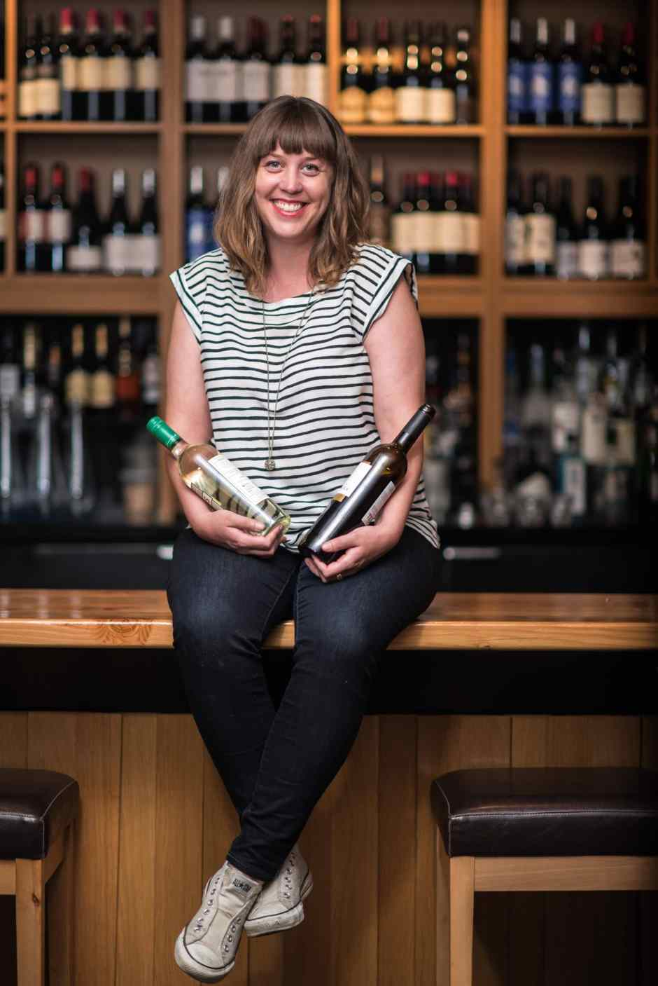 Meg sitting on a bar, holding two bottles of wine, smiling at the camera