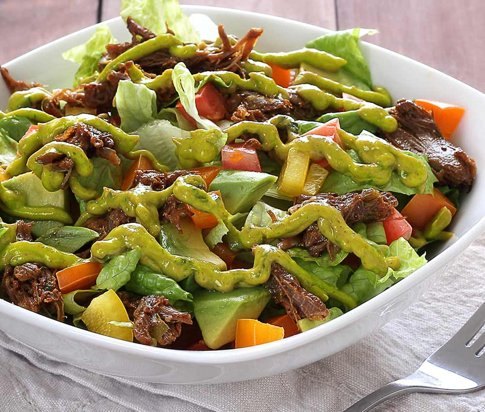 easy paleo and gluten free recipe for a shredded beef salad with avocado-lime dressing