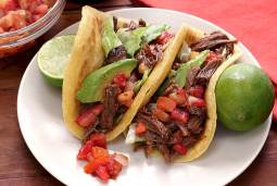 easy paleo shredded beef crockpot recipe, shown in a homemade gluten-free soft taco shell