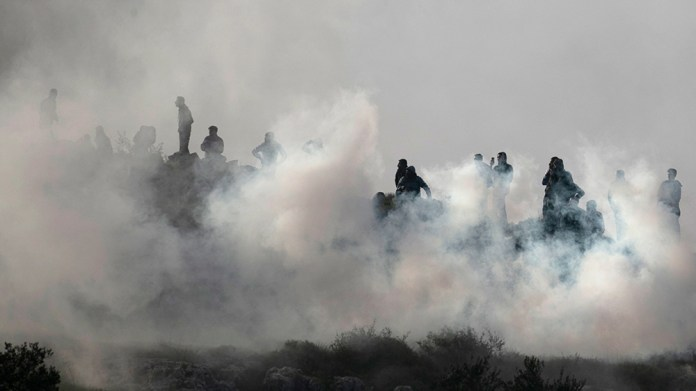 Palestinians stand in tear gas during clashes withIsraeli armed forces [Jaafar Ashtiyeh/AFP]