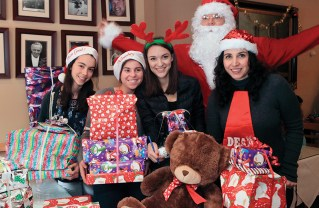 Palisades High seniors (left to right) Emma O'Neil, Madeline Goore and Ashley Miller and Vittorio's Vanessa Pellegrini helped Santa distribute Christmas toys to children.