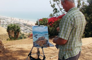 Russell Hunziker, a member of Allied Artists, paints on the bluffs. Photo: Matthew Stockman