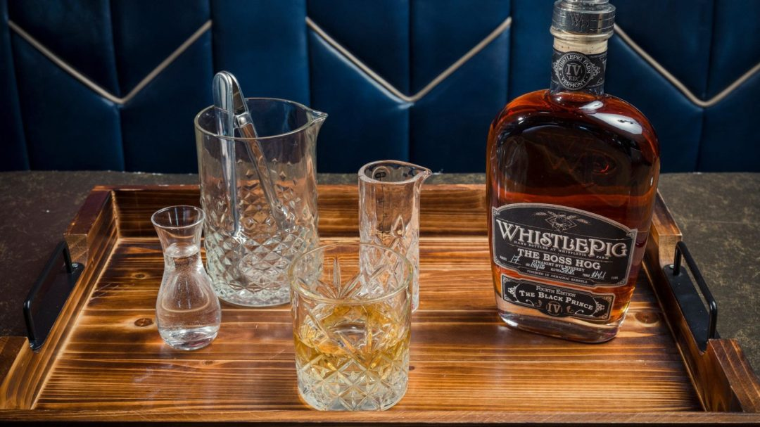 A photo of whistle pig and whisky on the rocks