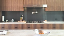 Kitchen Cabinets made with Walnut and Metal Backsplash and Stone Counter