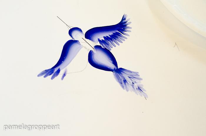 Painting wing feathers on blue bird in flight, pamela groppe art