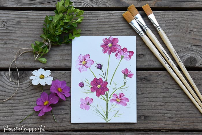 painting of cosmos flowers with brushes, boxwood cuttings and real cosmos flowers on wood surface