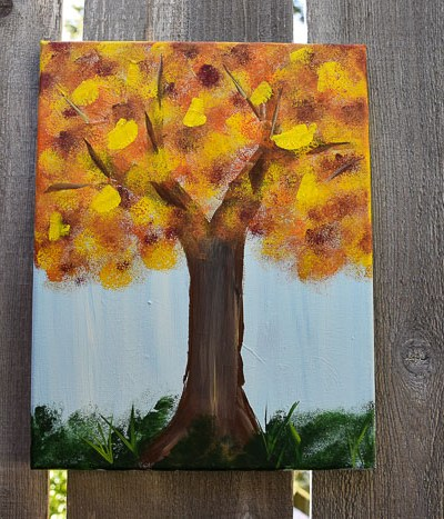 Fall tree painting hanging on fence