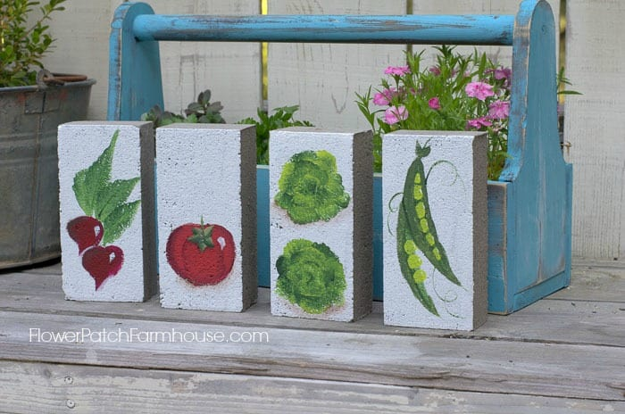 Bricks painted with vegetables as garden markers