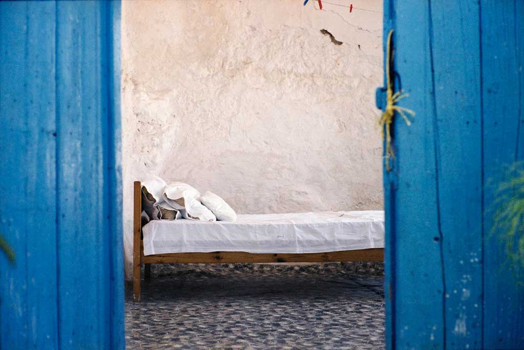 A blue doorway with no door shows a simple white bed in a white room