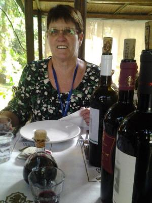 Judy at the winery with the sample bottles on the table beside her