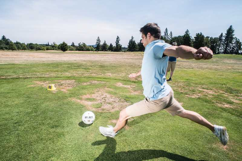 NEWS-TIMES PHOTO: CHASE ALLGOOD - Cory Toews kicks a soccer ball off the seventeenth tee.