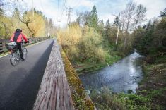TRIBUNE PHOTO: JONATHAN HOUSE - A bicyclist crosses over Johnson Creek on the Springwater Corridor Trail, near the Precision Castparts metals plants near Johnson Creek Boulevard in the Errol Heights neighborhood.
