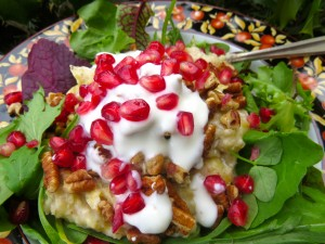 Warm cooked oats on top of fresh greens with yogurt ranch dressing garnished with pomegranate and pecans