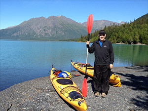 Pancreatic cancer survivor with kayaks by a lake