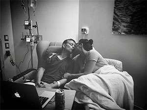 Jennifer bedside kissing her husband during chemo treatment in hospital