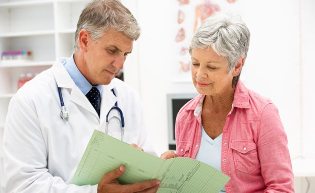 A doctor reviews potential risk factors with his patient including family history