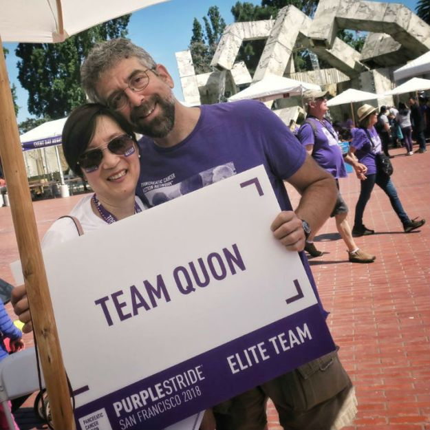 16-year survivor and husband hold a sign for walk to end pancreatic cancer in San Francisco