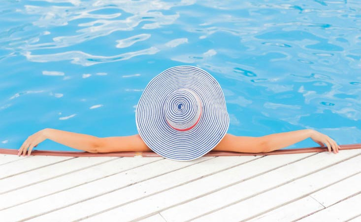 Woman lounging in swimming pool wearing a hat to protect her face and scalp from sun exposure