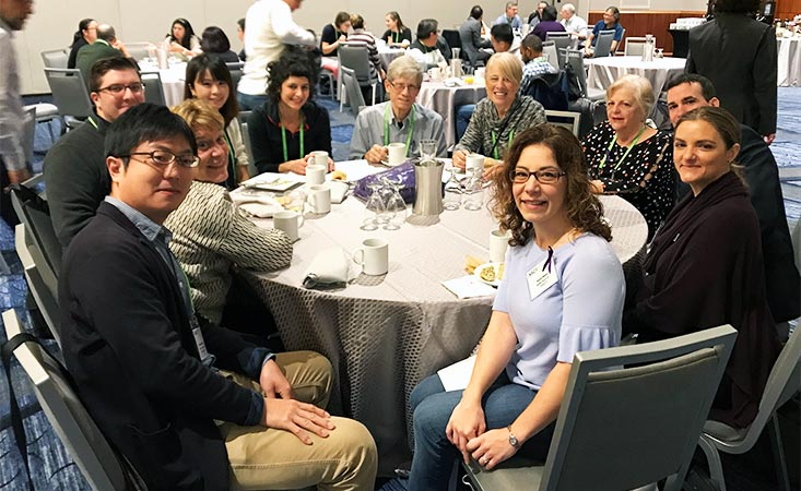 Group of men and women discuss pancreatic cancer research at a table over breakfast.