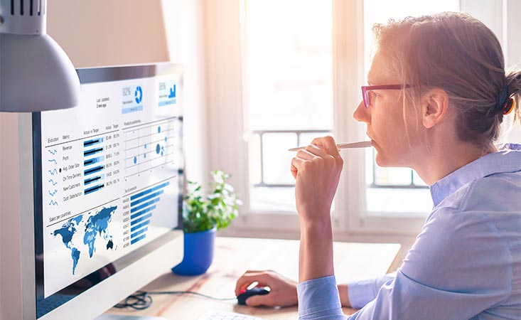 Woman is reviewing global cancer statistics and charts on her computer.