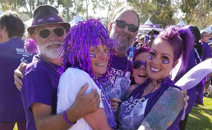 PurpleStride participants hug their teammate and pancreatic cancer survivor at the 5K walk.