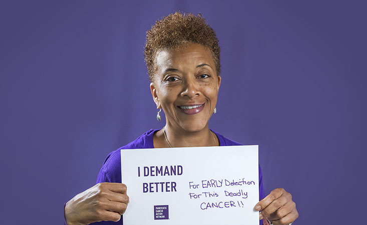 Volunteer holds a sign saying why she Demands Better for pancreatic cancer patients.