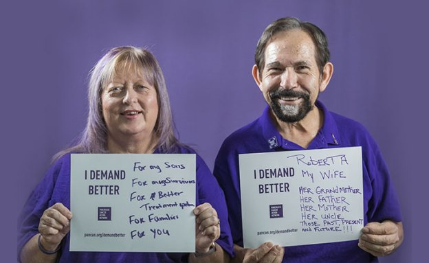 Pancreatic cancer volunteers hold signs saying why they Demand Better