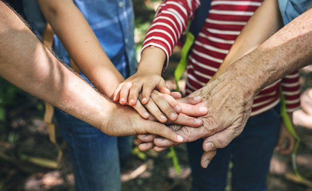 A multigenerational family puts their hands together to support pancreatic cancer awareness