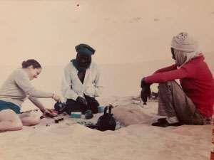 Caucasian woman having tea with Touareg men in Niger desert