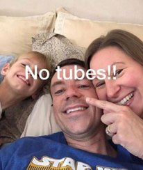 Husband lying in bed, flanked by wife and son.