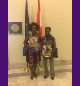 At the office of her member of Congress, Gloria holds a photo of her mother