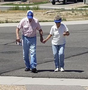 Caucasian couple in their 80s walking across wide, paved suburban street